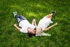 在爱的可爱的夫妇坐绿草 免版税图库摄影