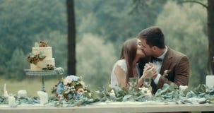 在爱的可爱的年轻夫妇在葡萄酒布料是轻轻地亲吻和握手在他们的在有雾的木头的日期期间 影视素材