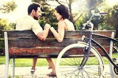 在爱的夫妇一起坐与自行车的一条长凳 库存照片