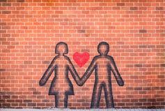 在爱的夫妇喷洒了在红砖墙壁上的油漆 免版税库存图片