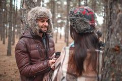 在爱的夫妇在一个冷的秋天森林里并且看彼此 免版税库存照片