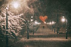 在爱的夫妇在一个浪漫日期通过有美丽的灯笼的多雪的夜冬天公园胡同走盖与 库存照片