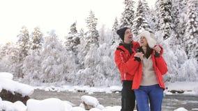 在爱的夫妇在一条山河附近在挥动冬天的森林里谈话和 影视素材