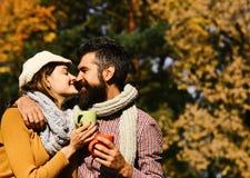 在爱的夫妇在公园拿着茶或咖啡 关系和热的饮料概念 女孩和有胡子的人 免版税图库摄影