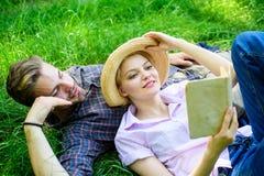 在爱的夫妇在公园花费休闲阅读书 人和女孩在草阅读书放置 家庭享受休闲与 库存照片