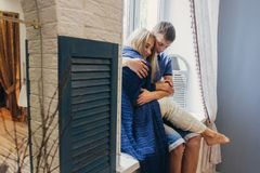在爱的夫妇在家坐窗口 嫩爱恋的embr 免版税图库摄影