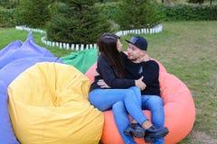 在爱的夫妇在扶手椅子,微笑,拥抱和k坐并且谈话 免版税库存照片