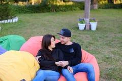 在爱的夫妇在扶手椅子,微笑,拥抱和k坐并且谈话 库存图片