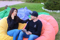 在爱的夫妇在扶手椅子,选出人的举行在手中坐并且谈话 库存图片