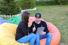 在爱的夫妇在扶手椅子,选出人的举行在手中坐并且谈话 免版税库存图片