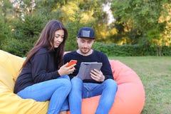 在爱的夫妇在扶手椅子,选出人的举行在手中坐并且谈话 免版税库存照片