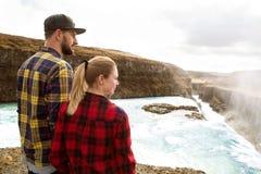 在爱的夫妇在日落的瀑布 库存图片