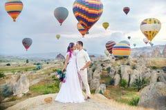 在爱的夫妇在气球背景站立在卡帕多细亚 供以人员和小山神色的一名妇女在很大数量的飞行气球 免版税库存照片
