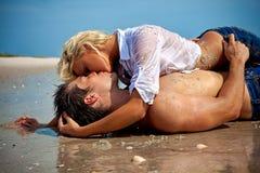 在爱的夫妇在海滩亲吻 免版税库存图片