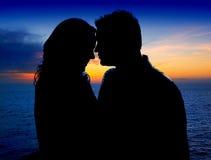 在爱的夫妇在海运的suset拥抱 免版税库存图片