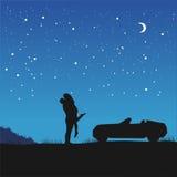在爱的夫妇在站立在他们的汽车旁边的拥抱在与星和月牙的夜空下 免版税库存照片