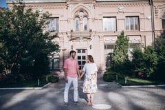在爱的夫妇在老城市站立 老大厦和绿色树在背景 握手和看彼此的夫妇 免版税库存照片