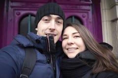 在爱的夫妇在背景做selfie门 库存图片