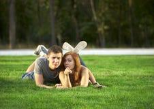 在爱的夫妇在草坪说谎在公园 免版税图库摄影