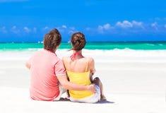 在爱的夫妇在蓝色海滩坐假期 库存照片