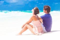 在爱的夫妇在蓝色海滩坐假期 免版税图库摄影