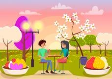 在爱的夫妇在表上坐日落在公园 皇族释放例证