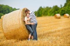 在爱的夫妇在黄色干草在夏天晚上调遣。 库存图片