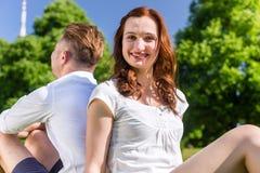 在爱的夫妇坐享用太阳的公园草坪 免版税库存图片