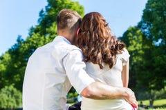 在爱的夫妇坐公园草坪享用 库存照片