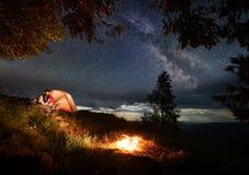 在爱的夫妇坐小山在享受灼烧的火的帐篷附近在夜空下撒布与明亮的星 库存照片