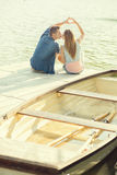 在爱的夫妇坐码头,他们的手显示心脏 库存照片