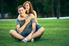 在爱的夫妇坐草坪 图库摄影