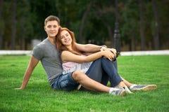 在爱的夫妇坐草坪 库存照片