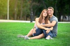 在爱的夫妇坐草坪 库存图片