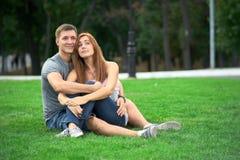 在爱的夫妇坐草坪 免版税库存图片