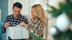 在爱的夫妇坐获得的窗台交换圣诞节礼物和乐趣 股票录像