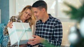 在爱的夫妇坐获得的窗台交换圣诞节礼物和乐趣 影视素材