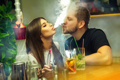 在爱的夫妇抽水烟筒并且喝鸡尾酒 库存图片