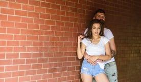 在爱的夫妇拥抱砖墙背景 夫妇是发现的地方单独的 他将从未让她走 女孩和行家 免版税库存图片