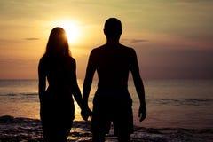 在爱的夫妇支持在海的轻的剪影 免版税库存图片
