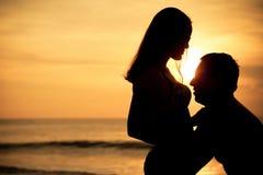 在爱的夫妇支持在海的轻的剪影 免版税图库摄影