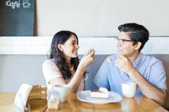 在爱的夫妇有蛋糕在咖啡馆 免版税库存照片