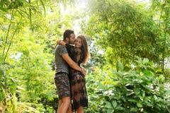 在爱的夫妇站立在日落在密林 图库摄影