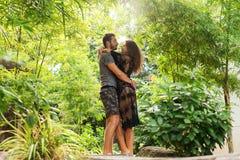 在爱的夫妇站立在日落在密林 免版税库存照片