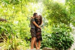 在爱的夫妇站立在日落在密林 库存照片