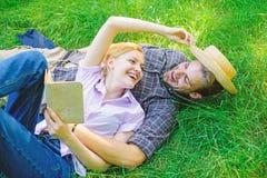 在爱的夫妇花费休闲阅读书 在草放松和女孩放置的人 浪漫夫妇家庭享受休闲与 免版税库存照片