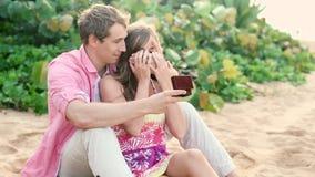 在爱的夫妇,供以人员惊奇他的有定婚戒指的伙伴在海滩