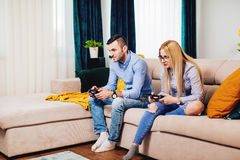 在爱的夫妇 与现代生活方式的幸福和赌博概念 打在电视控制台的夫妇数字式比赛 免版税库存照片