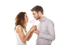 在爱的夫妇从被隔绝的同一块玻璃喝 库存图片