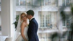 在爱的婚礼夫妇 白色户内礼服英俊的新郎容忍的美丽的新娘在装饰的演播室室白色 影视素材